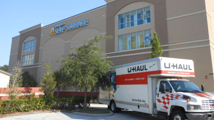 Uhaul truck parked in front of a Compass Self Storage facility.