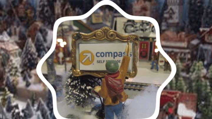 Christmas figurine looks at mini Compass Self Storage sign.