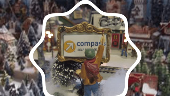 Christmas figurine looks at mini Compass Self Storage sign.