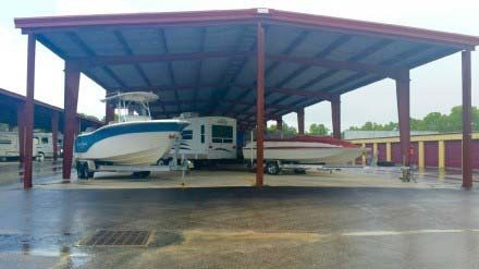Boats and RV parked in covered storage area.