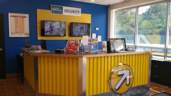 Compass Self Storage rental office with security monitors.