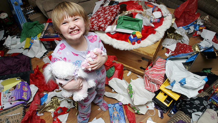 Child smiling in the middle of a messy room after opening presents.