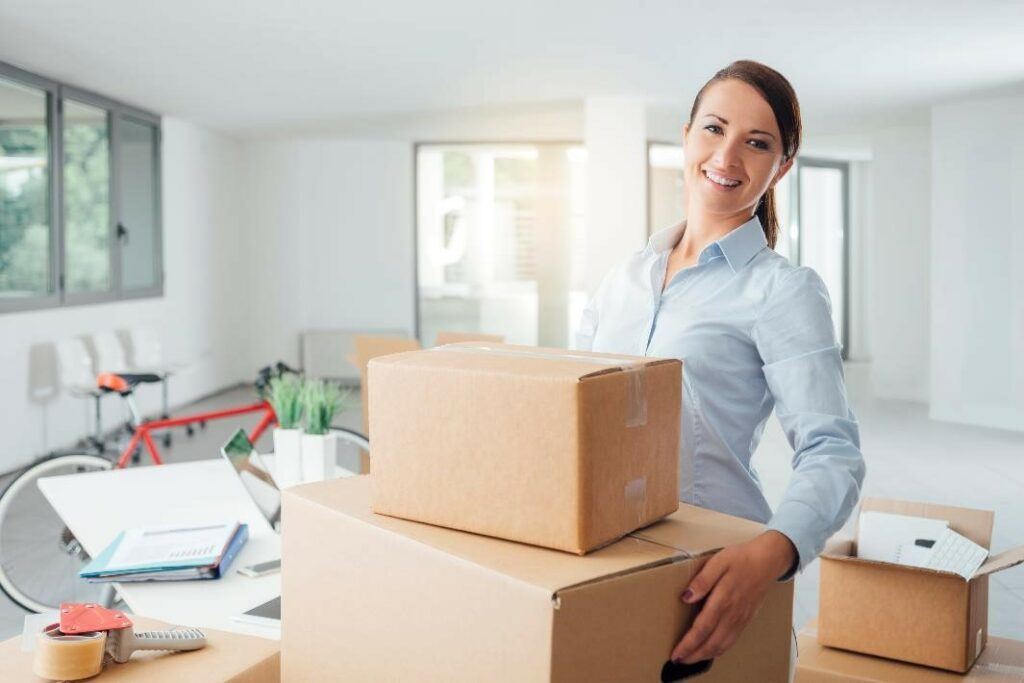 Smiling woman with moving boxes.