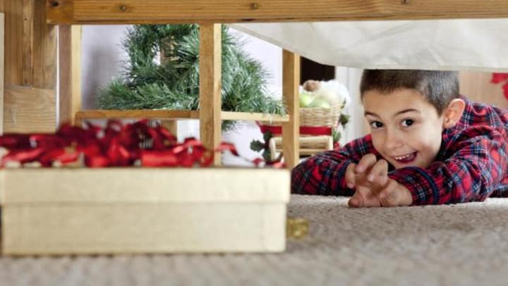 Young boy reaching for a present hidden under a bed.