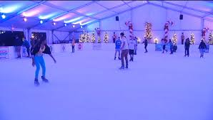 Group of people ice skating indoors during the winter.