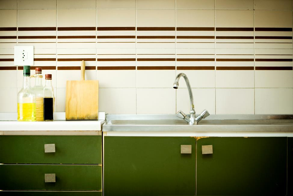 Three cooking bottles and cutting board sitting beside a sink.