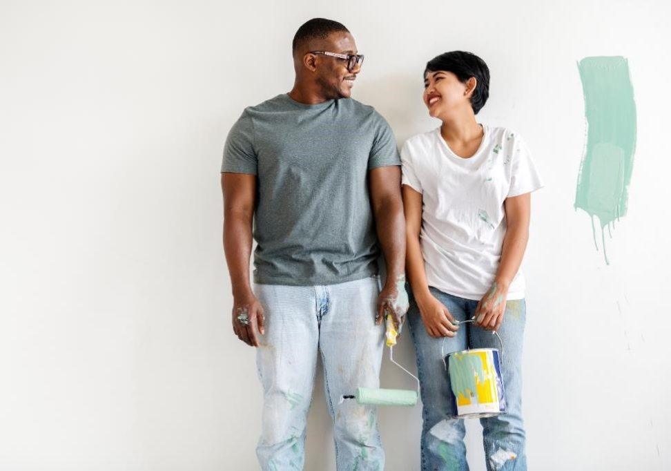 Smiling couple painting a room.