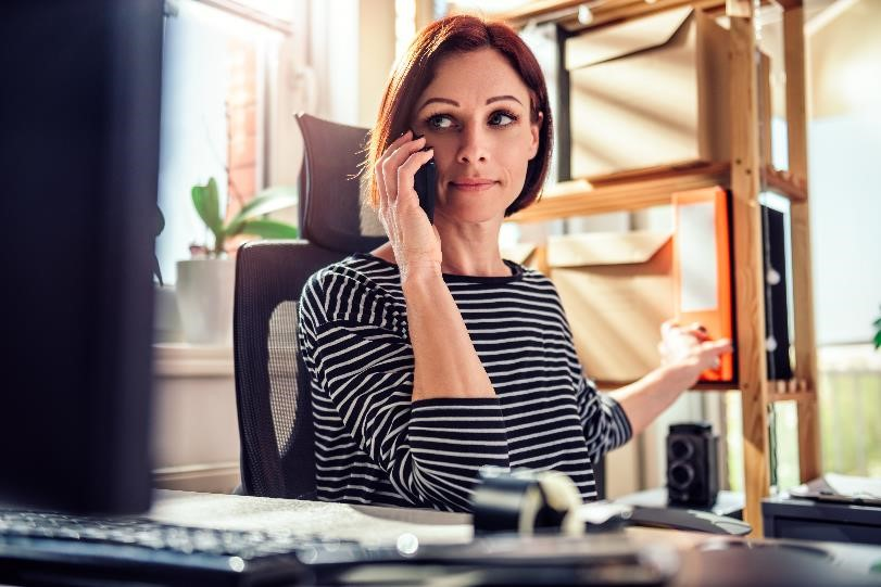 Business woman sitting in front of work computer while talking on the phone.