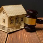 Miniature model of house sitting on table next to an auction gavel.