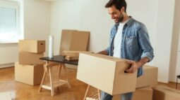 Man smiling while moving boxes out of house.