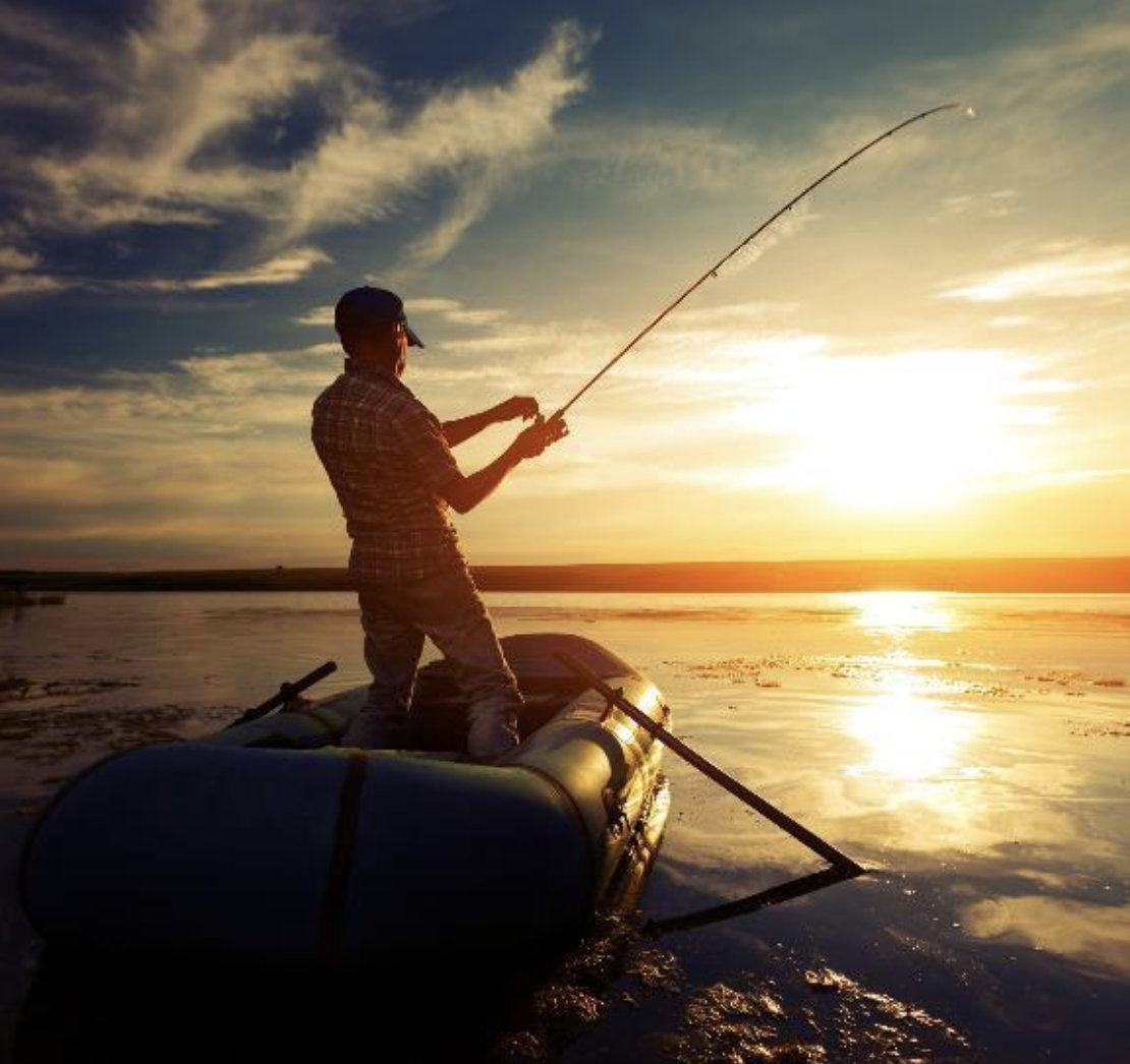 a man casts his fishing rod into a lake at sunset