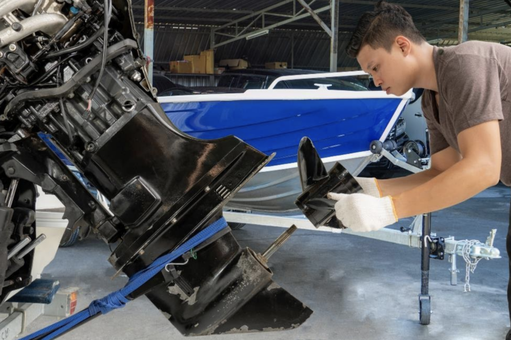 a man is performing maintenance on his boat motor and rudder