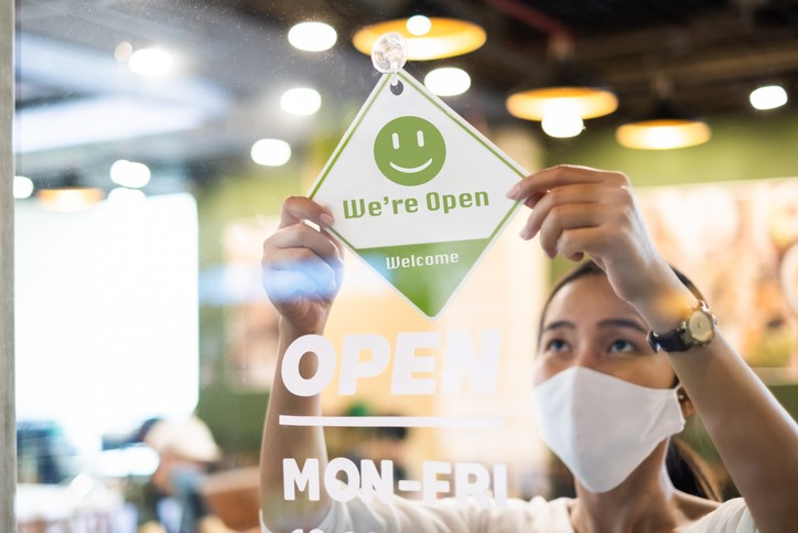 a female restaurant worker wearing a mask is flipping over the restaurant's sign to let customers know the restaurant is open