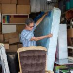 a man is reorganizing his storage unit that's packed with boxes, furniture, and a mattress
