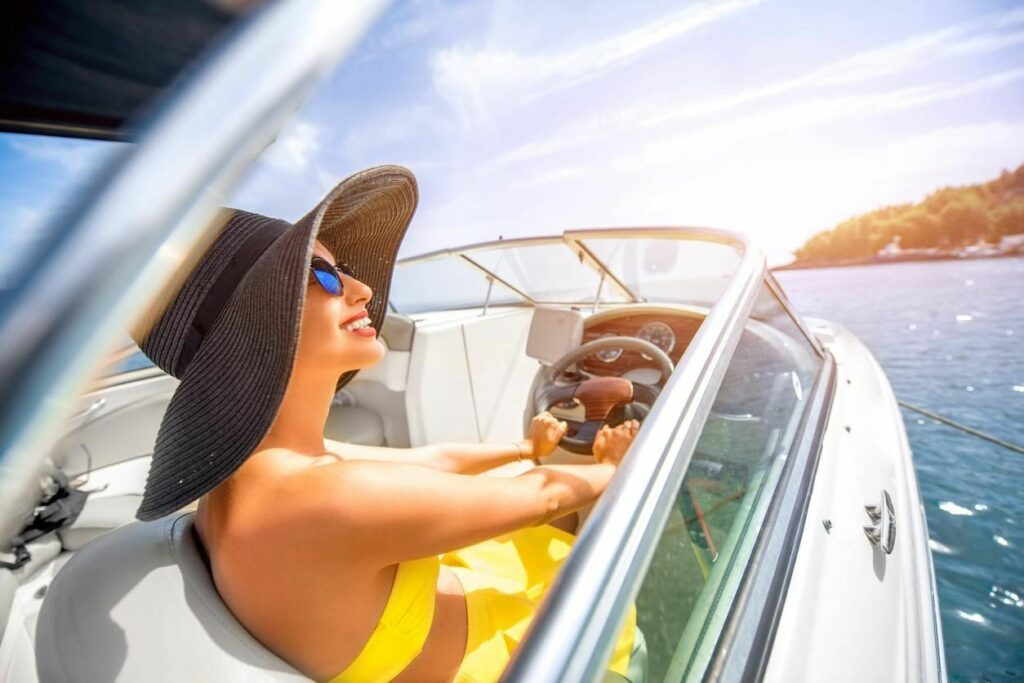 a woman turns her face toward the florida sun as she enjoys riding on a boat across calm ocean waters