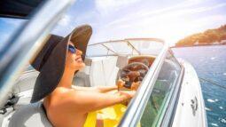 a woman turns her face toward the florida sun as she enjoys riding on a boat across calm ocean waters