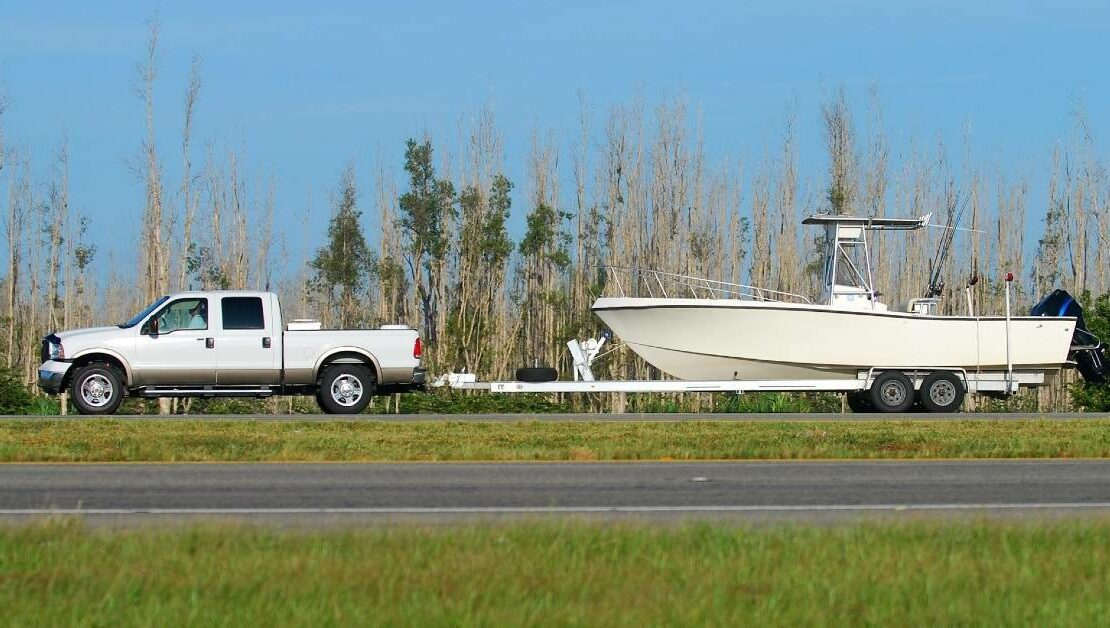 Florida boat owner towing vessel behind truck to Miami boat storage space